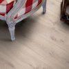 Laminat Pergo Long Plank Eik Modern Grey 1 stav. Nærbilde av stol på gulv.
