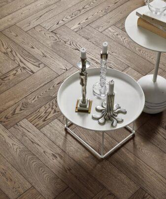 Fiskebensparkett Tarkett Segno Eik Old Grey. Nærbilde av gulv med bord.