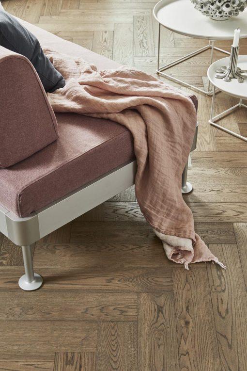 Fiskebensparkett Tarkett Segno Eik Old Grey. Nærbilde av stol på gulv.