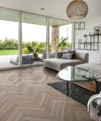 Vinylgulv Kährs Luxury Tiles Whinfell Fiskebenmønster. Foto av gulv i stue.