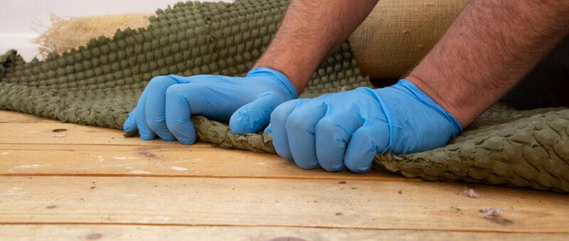 Foto av teppe som fjernes fra tregulv.